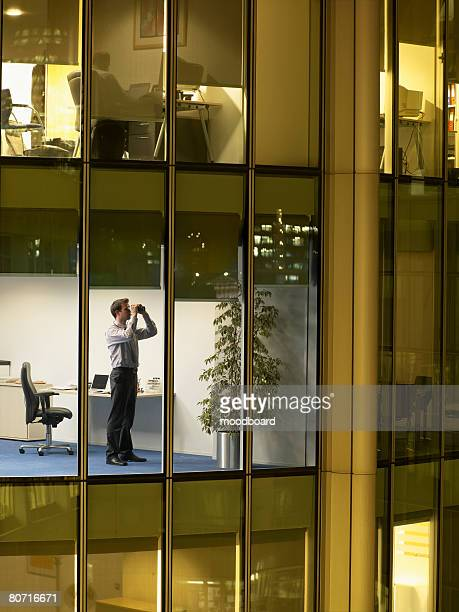 Businessman in Office Looking Through Binoculars