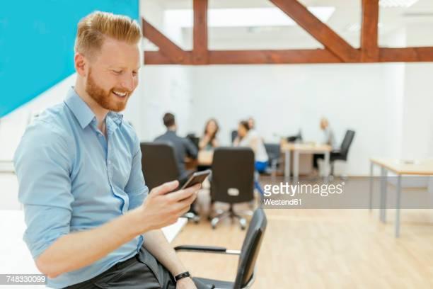 Businessman in office meeting using smartphone
