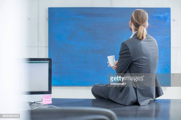 businessman in office sitting on desk looking at a blue painting - art dealer stock pictures, royalty-free photos & images