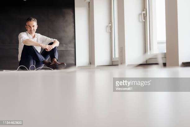 businessman in office sitting on the floor - focus on background stock pictures, royalty-free photos & images