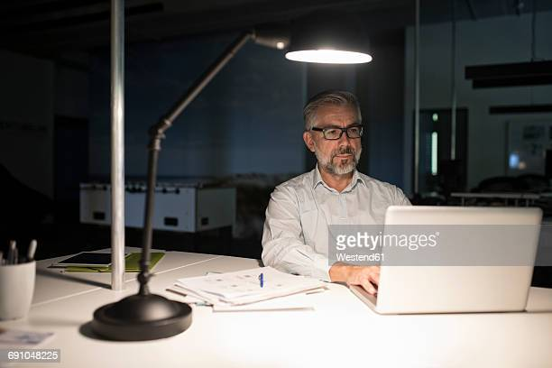 businessman in office using laptop in the dark - lamp stock-fotos und bilder