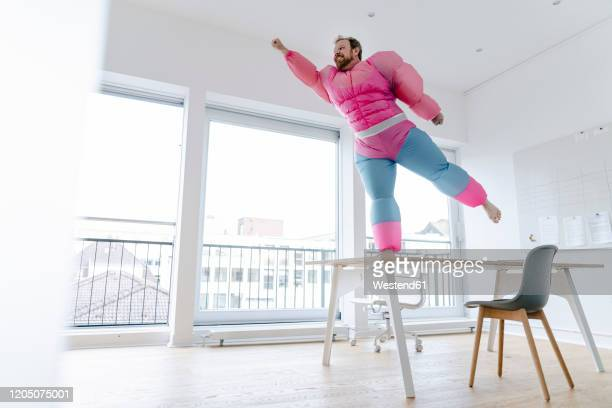 businessman in office wearing pink bodybuilder costume pretending to fly - kraft stock-fotos und bilder