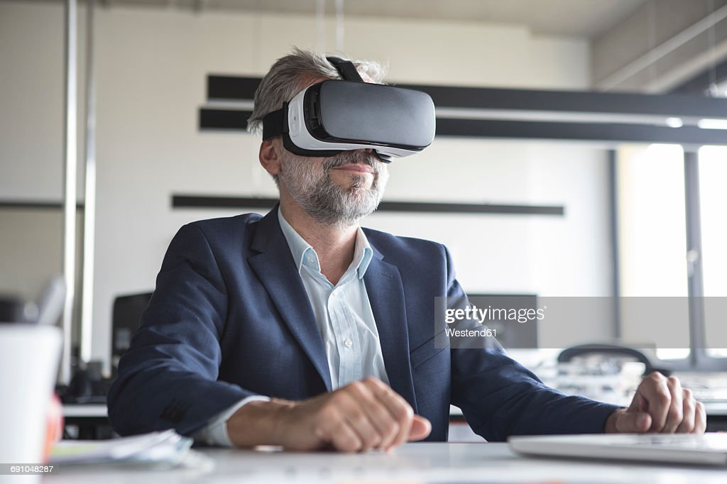 Businessman in office wearing virtual reality glasses : Stock Photo