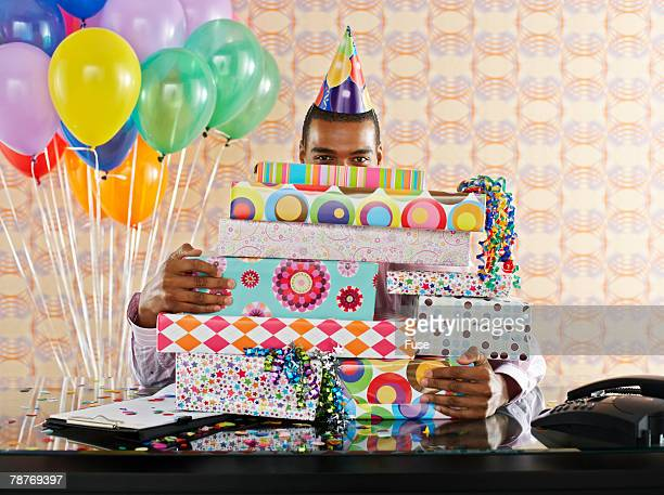 Businessman In Office With Birthday Gifts Stock Photo