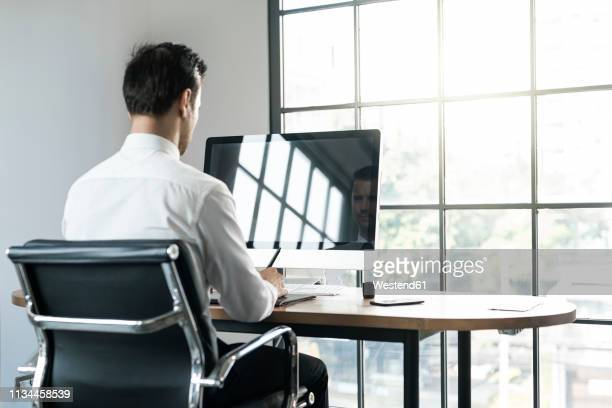 businessman in office working on computer in front of window - ビジネスウェア ストックフォトと画像