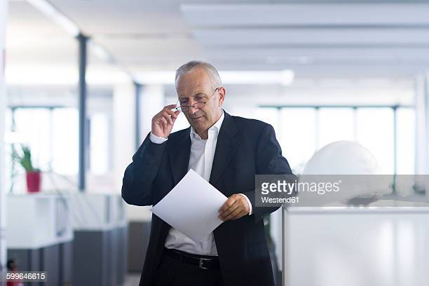 Businessman in open space office reading document