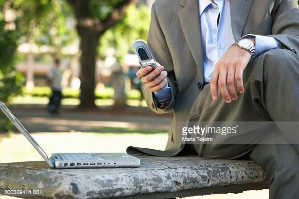 Businessman in park using laptop and mobile phone, mid section