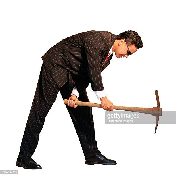 Businessman in pinstripe suit using pick-axe