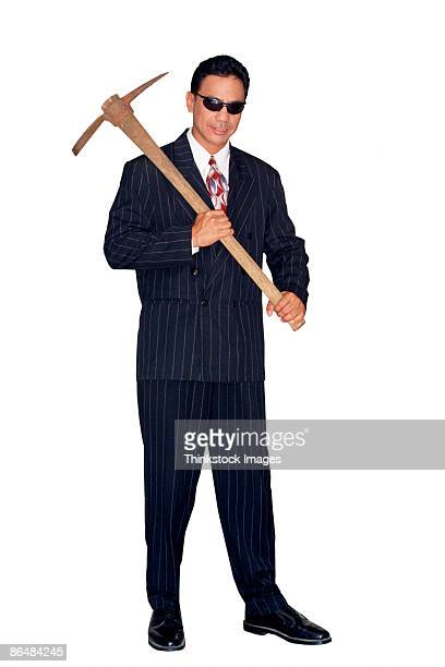 Businessman in pinstripe suit with pick-axe