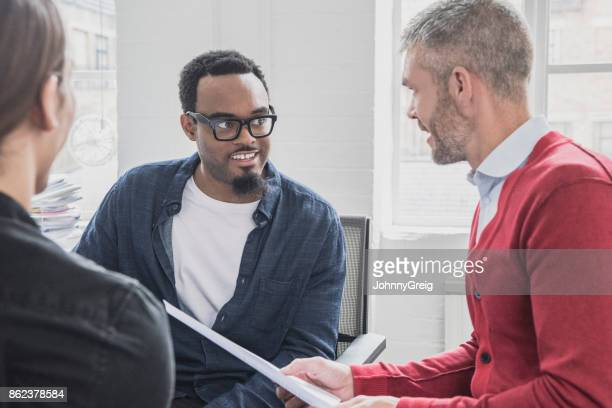 Businessman in red cardigan talking to African colleague in glasses