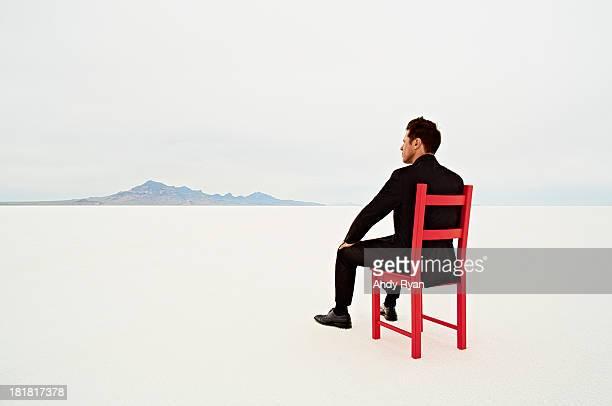 Businessman in red chair in desert, facing horizon