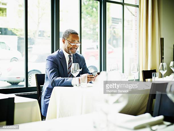 Businessman in restaurant looking at smart phone