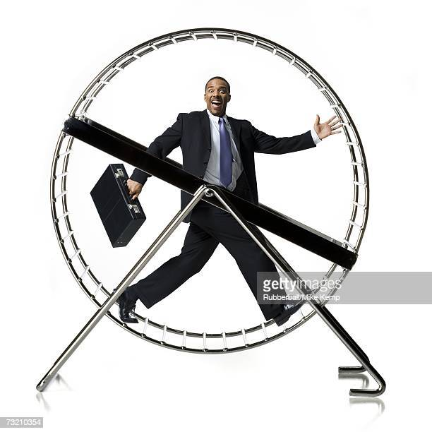 Businessman in rodent wheel smiling