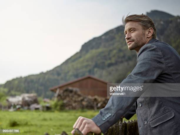 businessman in rural landscape looking at view - elegante kleidung stock-fotos und bilder