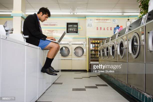 businessman in shorts sitting on washer with laptop at launderette - shorts stock pictures, royalty-free photos & images