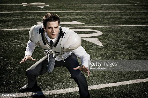 Businessman in Shoulder Pads on Football Field