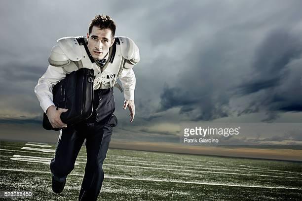 Businessman in Shoulder Pads Running on Football Field