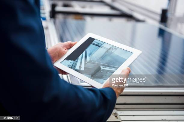 businessman in solar factory holding tablet - energieindustrie stock-fotos und bilder