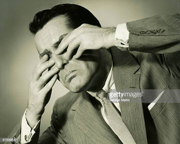 Businessman in studio covering eyes with fingers, (B&W), close-up
