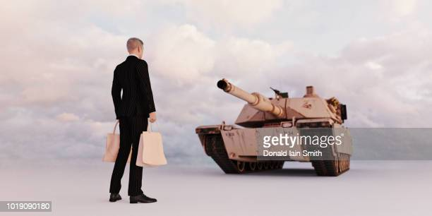 businessman in suit carrying shopping bags standing in front of tank - armored tank foto e immagini stock