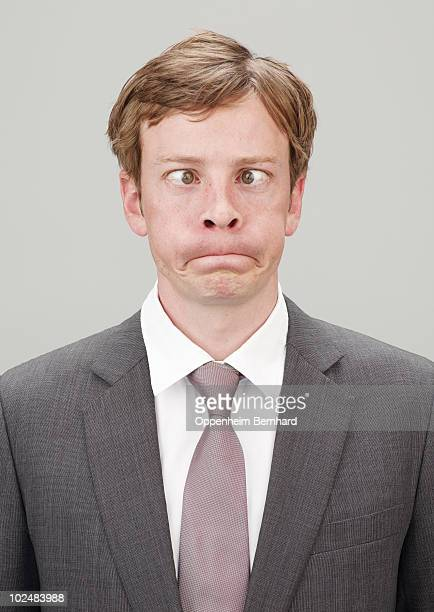 businessman in suit going cross eyed