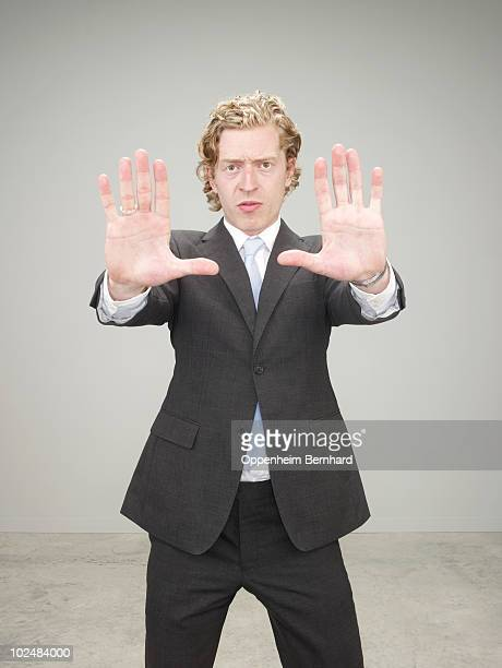 businessman in suit holding palms of hands out