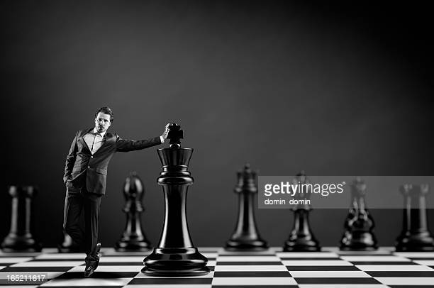 Businessman in suit leans hand on Chess King, black white