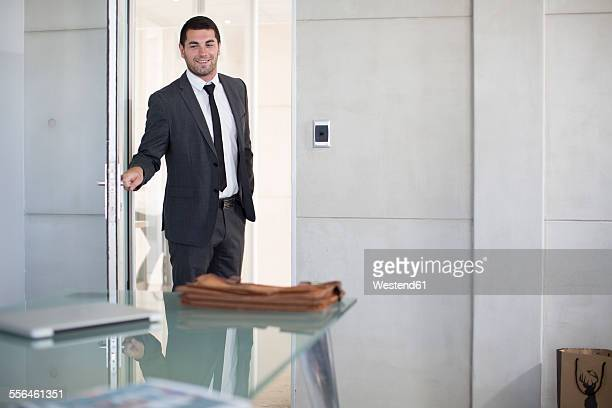 Businessman in suit opening boardroom door