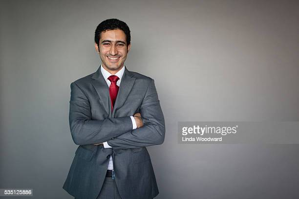 Businessman in suit standing against grey background.