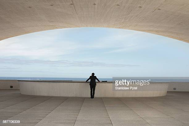 businessman in suit standing near ocean - stability stock pictures, royalty-free photos & images