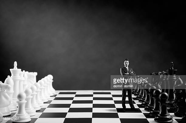 Businessman in suit standing on Chess Board near Chess Pieces