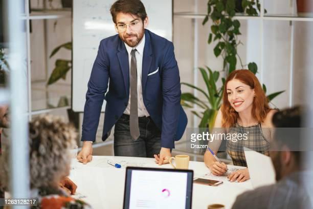 homme d'affaires en costume parlant à ses collègues après la pandémie de coronavirus - groupe moyen de personnes photos et images de collection