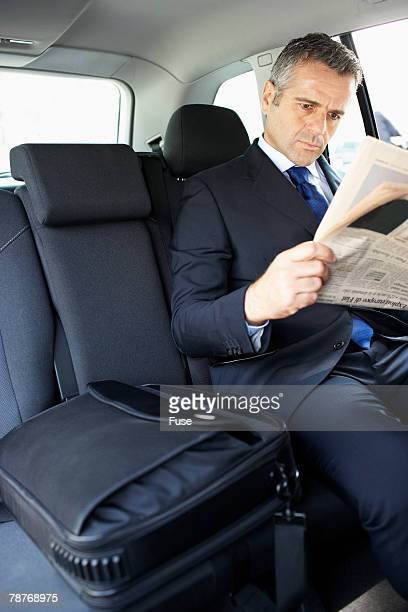 Businessman in Taxi Reading Newspaper
