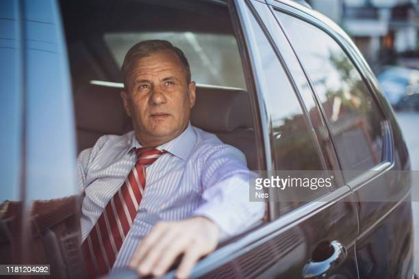a businessman in the back seat of a car while driving - ascot stock pictures, royalty-free photos & images