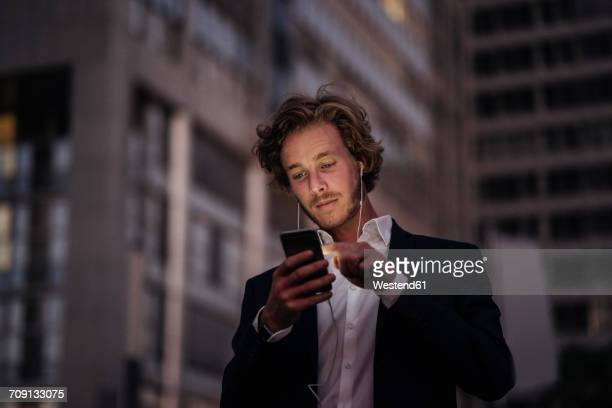 Businessman in the city at dusk using cell phone