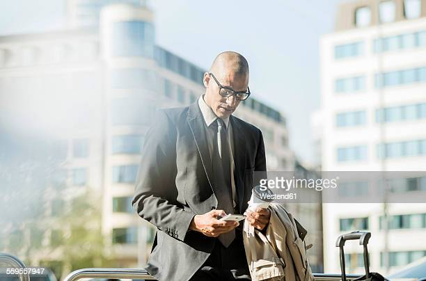 Businessman in the city looking on smartphone