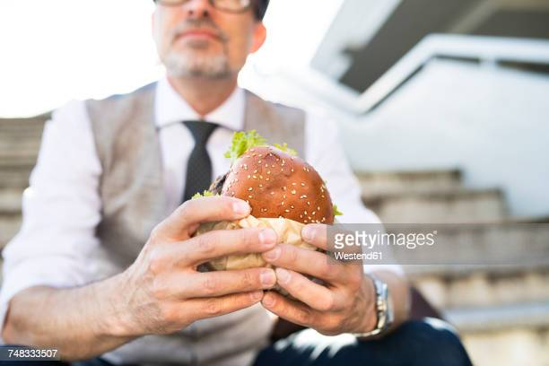 Businessman in the city sitting on stairs eating a hamburger