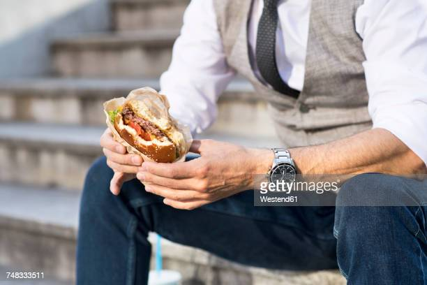 businessman in the city sitting on stairs eating a hamburger - unhealthy living stock pictures, royalty-free photos & images