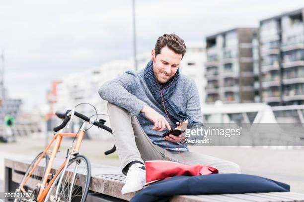 businessman in the city with bicycle using smartphone and earphones - equipamento de lazer - fotografias e filmes do acervo
