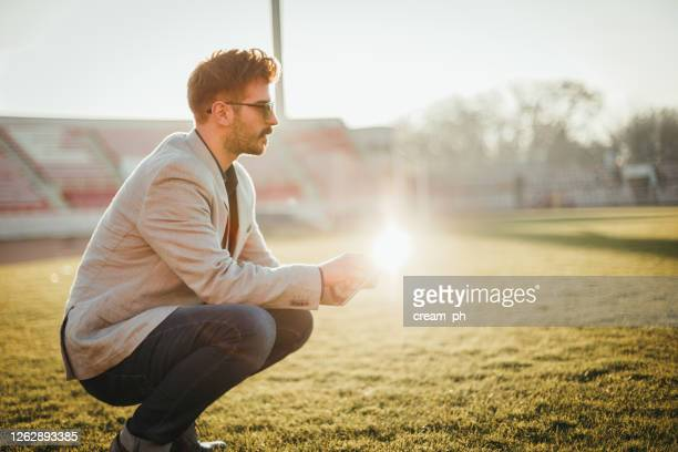 businessman in the empty soccer field using digital tablet - audience free event stock pictures, royalty-free photos & images