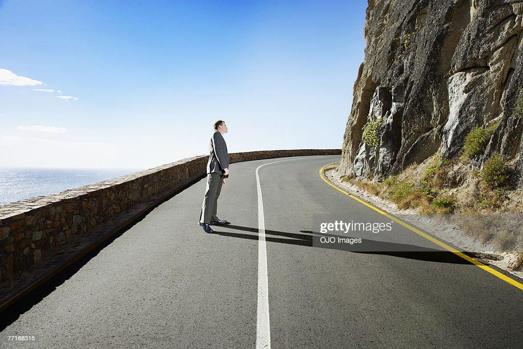 A businessman in the middle of the road peeking around the corner : Stock Photo