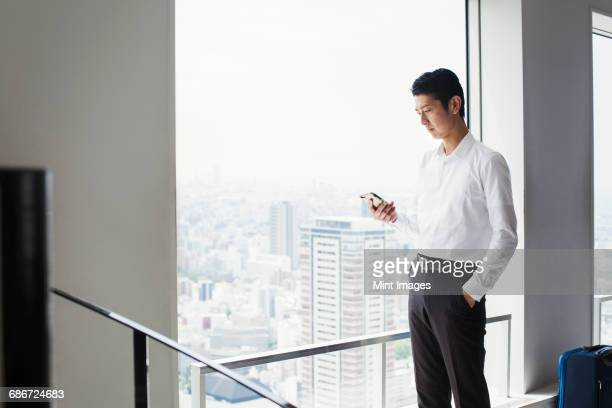 A businessman in the office, by a large window, looking at his smart phone.