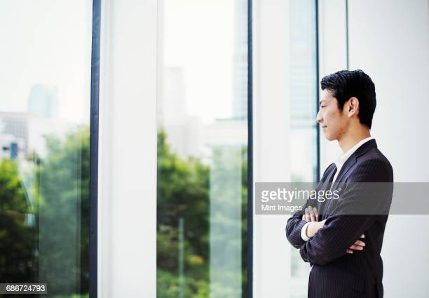 A businessman in the office, by a large window, looking out.