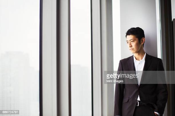 A businessman in the office, by a large window, looking over the city.