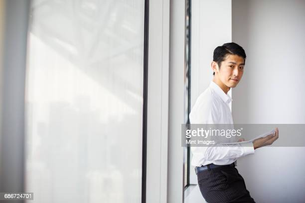 A businessman in the office, by a large window, using his smart phone.