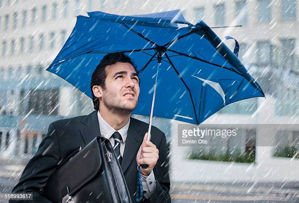 Businessman in the rain with broken old umbrella