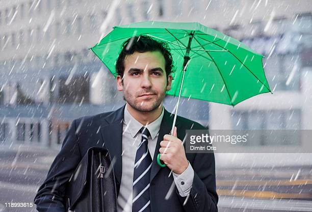 businessman in the rain with small umbrella - too small stock pictures, royalty-free photos & images