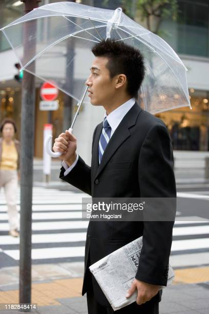 a businessman in the street with an umbrella - 背広 ストックフォトと画像