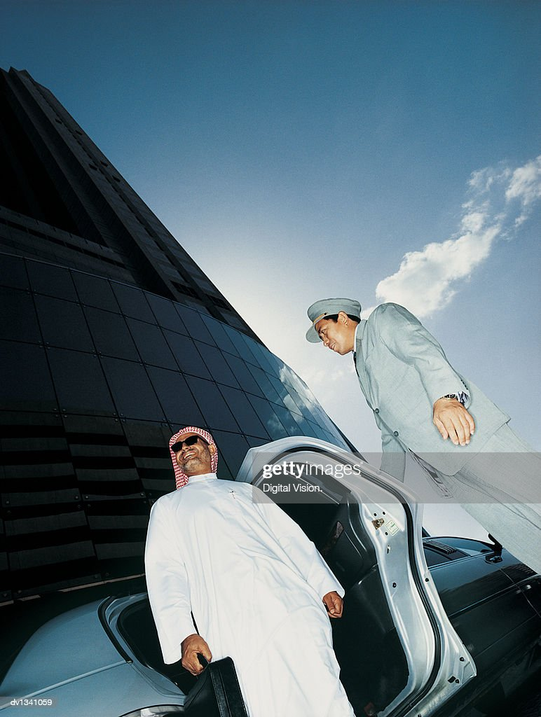 Businessman in Traditional Middle Eastern Dress Alighting From His Limousine, Helped By His Chauffeur : Stock Photo