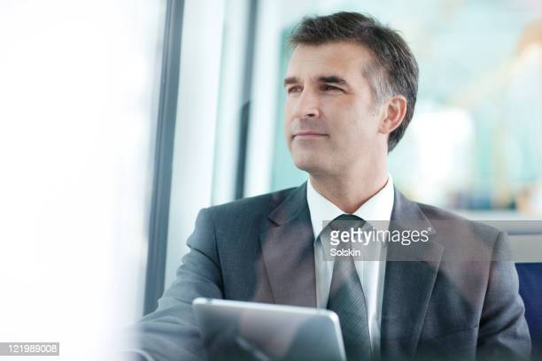 businessman in train, holding tablet computer